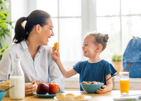 Healthy food at home. Happy family in the kitchen. Mother and child daughter are having breakfast before school. 免版税图像