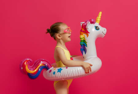 Happy child wearing swimsuit. Girl with swimming ring flamingo. Kid on a colored pink background. 免版税图像