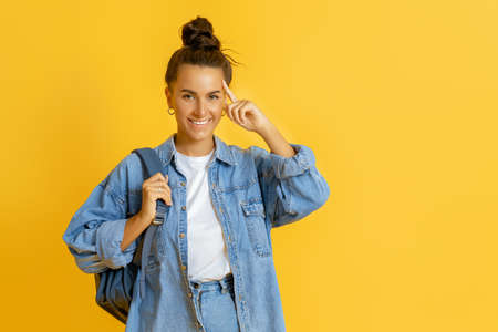 Happy emotional young woman posing and laughing on bright yellow background