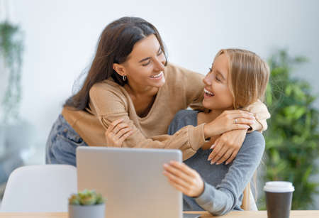 Two happy young women using laptop. Friends spending time together. 免版税图像