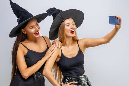 Happy Halloween! Two young women in black witch costumes taking selfie on white wall background.
