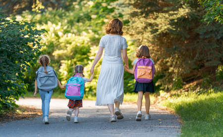 Parent and pupils of primary school go hand in hand. Woman and girls with backpacks behind backs. Beginning of lessons. First day of fall.
