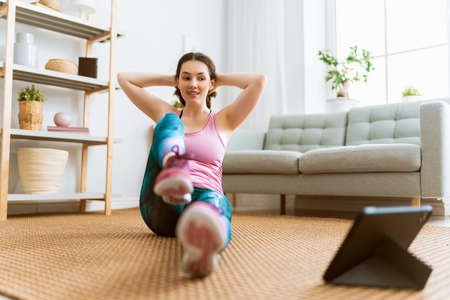 Young woman in activewear watching online courses on tablet while exercising at home.