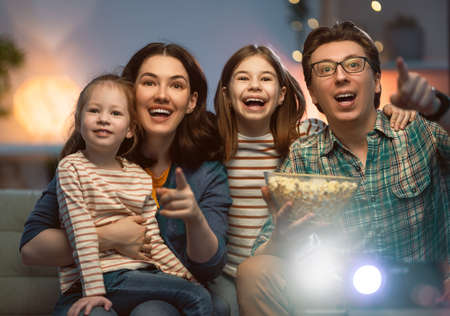 Happy family watching projector, TV, movies with popcorn in the evening at home. Mother, father and daughters spending time together.