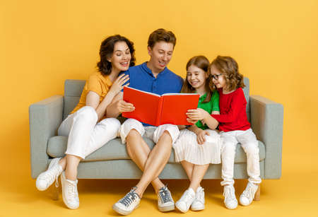 Happy loving family. Mother, father and children daughters reading a book on yellow background. 免版税图像