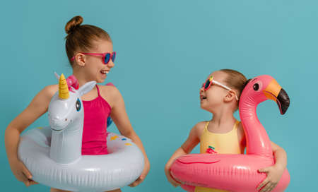 Happy children wearing swimsuit. Girls with swimming rings unicorn and flamingo. Kids on a colored turquoise background. 免版税图像