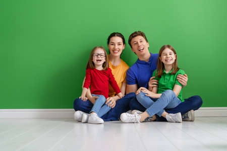 Happy loving family. Mother, father and children daughters on green background.