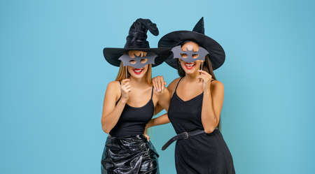 Happy Halloween! Two young women in black witch costumes on party on teal color background.
