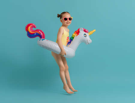 Happy child wearing swimsuit. Girl with swimming ring unicorn. Kid on a colored turquoise background. 免版税图像