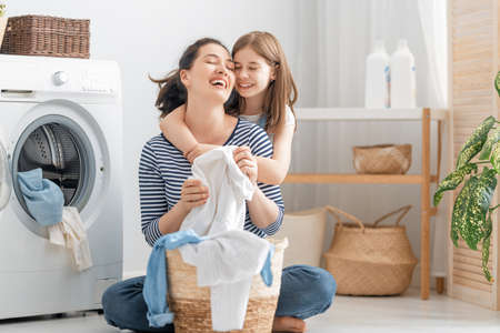 Beautiful young woman and child girl little helper are having fun and smiling while doing laundry at home. 免版税图像