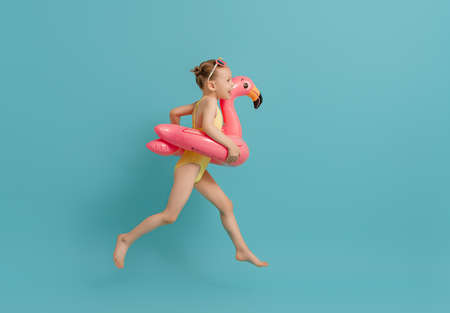 Happy child wearing swimsuit. Girl with swimming ring flamingo. Kid on a colored turquoise background.