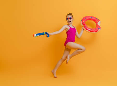 Happy child wearing swimsuit. Girl with swimming ring donut. Kid on a colored yellow background. 免版税图像