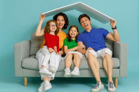 Mother, father and children girls with a symbol of roof on bright color background. Concept of housing for young family.