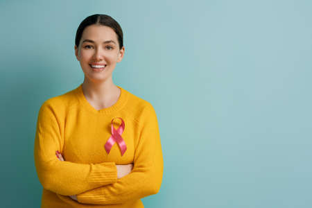 Young woman on color turquoise background. Pink ribbon like a symbol of cancer awareness. Support people living with tumor illness.