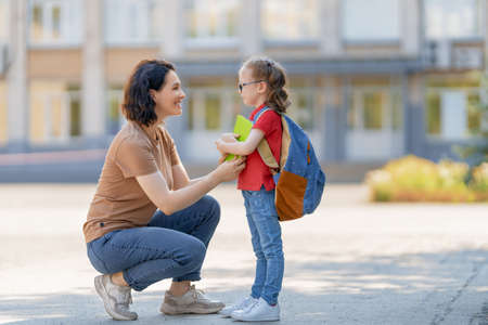 Parent and pupil of primary school go hand in hand. Woman and girl with backpack behind the back. Beginning of lessons. First day of fall.