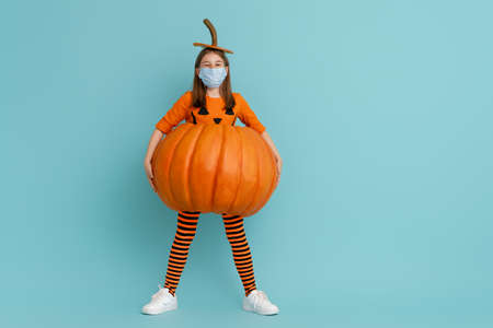 Happy Halloween! Cute little girl in pumpkin costume  wearing face mask protecting from COVID-19.