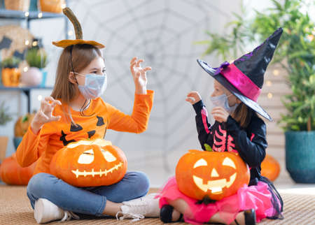 Cute little children girls in carnival costumes wearing face masks. Happy family preparing for Halloween protecting from COVID-19.