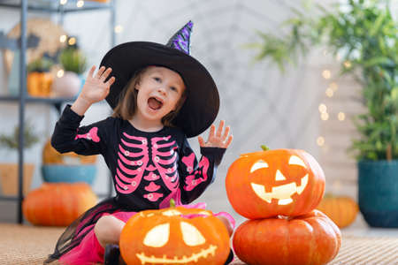 Cute little child with carving pumpkin. Happy girl preparing for Halloween. Funny kid at home.