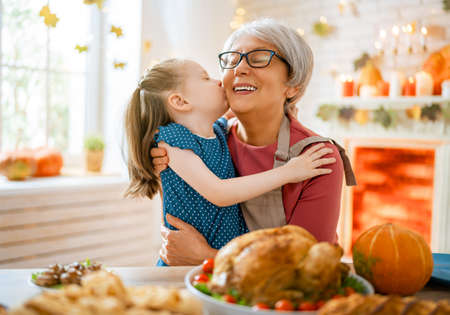 Happy Thanksgiving Day! Autumn feast. Family sitting at the table and celebrating holiday. Traditional dinner. Grandmother and granddaughter.