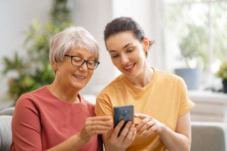 Young and senior women are using smartphone. Daughter is helping mother having fun staying at home. Stock Photo