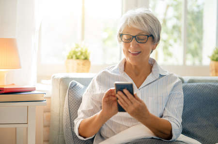 Joyful beautiful senior woman is using smartphone sitting on the bed at home. Stock Photo