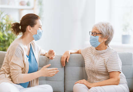 Adult daughter and senior parent wearing facemasks during coronavirus and flu outbreak. Virus and illness protection, home quarantine. COVID-2019
