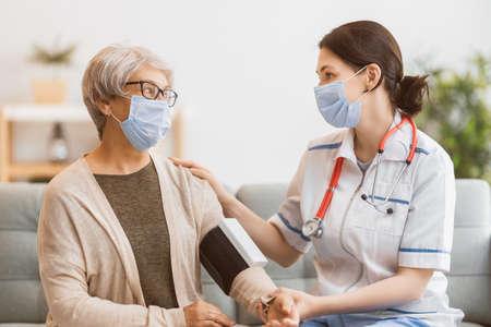 Elderly patient and doctor measuring blood pressure. Reklamní fotografie