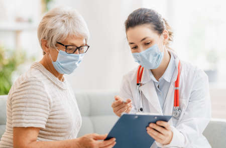 Doctor and senior woman wearing facemasks during coronavirus and flu outbreak. Virus protection. COVID-2019. Taking on masks. Foto de archivo