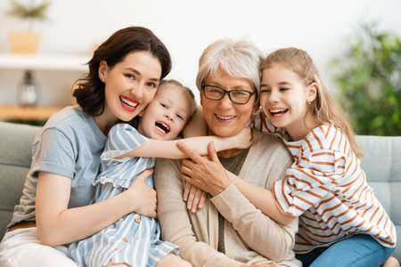 A nice girls, their mother and grandmother enjoying spending time together at home.