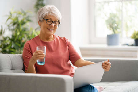Joyful beautiful senior woman is using laptop sitting on the sofa at home. Standard-Bild