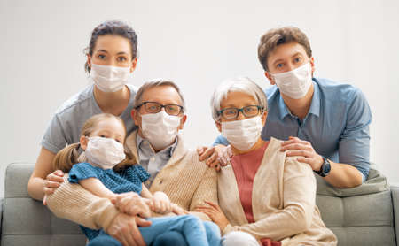 Family is wearing facemasks during coronavirus and flu outbreak. Virus and illness protection, quarantine. COVID-2019. A call to stay at home Foto de archivo