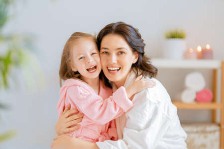 Happy family! Mother and daughter child girl are caring for skin in the bathroom. Standard-Bild