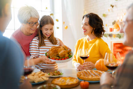 Happy Thanksgiving Day! Autumn feast. Family sitting at the table and celebrating holiday. Grandparents, mother, father and children. Traditional dinner.