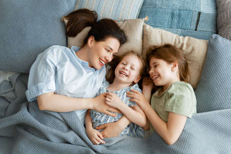 A nice girls and their mother enjoy sunny morning. Good time at home. Children waking up from sleep. Family playing on the bed in the bedroom. Archivio Fotografico