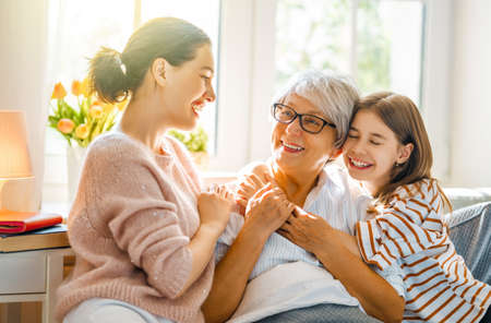 A nice girl, her mother and grandmother enjoying spending time together at home. Archivio Fotografico