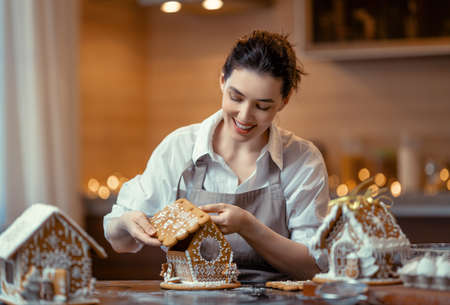 Merry Christmas and Happy Holidays. Family preparation holiday food. Woman cooking gingerbread house. Imagens