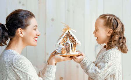 Happy little girl and her mother with Christmas gingerbread house on white wooden background.