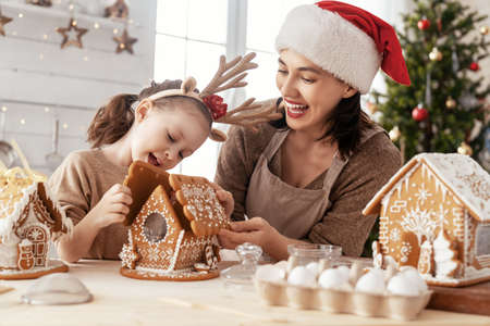 Merry Christmas and Happy Holidays. Family preparation holiday food.Mother and daughter cooking gingerbread house.