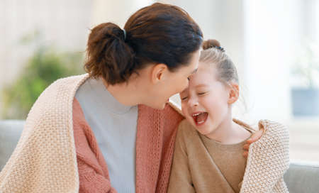 Happy time at home. Mom and her daughter child girl are playing, smiling and hugging. Family holiday and togetherness. Stok Fotoğraf
