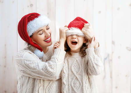 Happy little girl and her mother in Santa's hats on white wooden background.