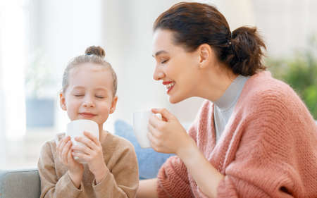 Happy time at home. Mom and her daughter child girl are enjoying hot beverages. Family holiday and togetherness.