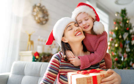 Merry Christmas and Happy Holidays! Cheerful mom and her cute daughter girl exchanging gifts. Parent and little child having fun near tree indoors. Loving family with presents in room.