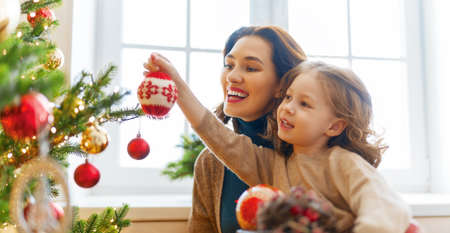 Merry Christmas and Happy Holidays! Mom and daughter near the tree indoors. The morning before Xmas. Portrait loving family close up. Stok Fotoğraf