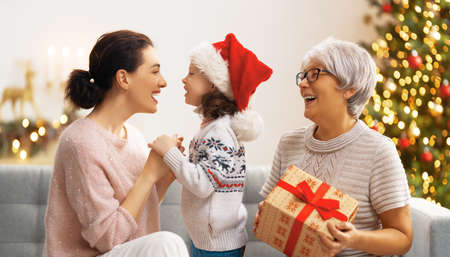 Merry Christmas and Happy Holidays! Cheerful kid presenting gifts to mom and granny. Parents and little child having fun near tree indoors. Loving family with presents in room.