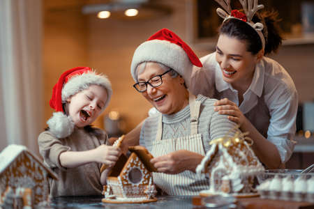 Merry Christmas and Happy Holidays. Family preparation holiday food. Grandma, mother and daughter cooking ginger house. Stok Fotoğraf