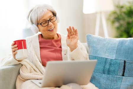Joyful beautiful senior woman is using laptop sitting on the sofa at home.