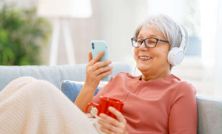 Senior woman listening to music in headphones sitting on the sofa in the room at home.