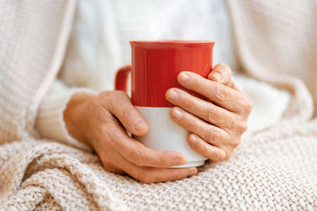 Senior woman with a mug in hands close up. Winter warming up concept. Stok Fotoğraf