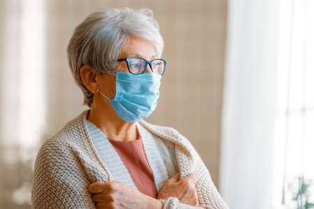 Senior woman wearing facemask during coronavirus and flu outbreak. Virus and illness protection, home quarantine. COVID-2019. Taking on or taking off masks.