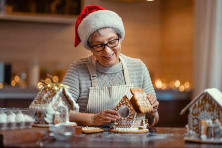 Merry Christmas and Happy Holidays. Family preparation holiday food. Woman cooking gingerbread house.